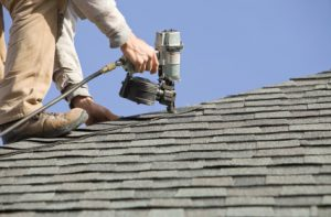 Man working on roof with nail gun. Fredericksburg Roofers 540-412-7332