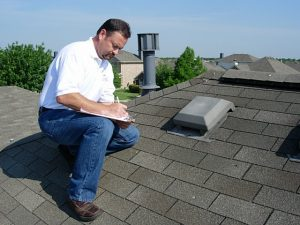 Licensed Roof Inspector in Fredericksburg, Virginia taking notes on a residential roof.