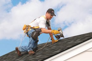 Worker repairing hail damage on shingle home in Fredericksburg, Virginia - Fredericksburg Roofers